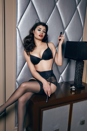 Beautiful sexy tanned brunette woman with  in black lace lingerie with a beautiful evening makeup sitting on the table next to wall hand strap with shoulder red lips perfect body Stock Photo