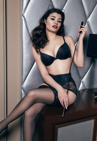 powder room: Beautiful sexy tanned brunette woman with  in black lace lingerie with a beautiful evening makeup sitting on the table next to wall hand strap with shoulder red lips perfect body Stock Photo