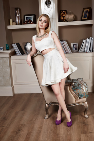 chic woman: Beautiful sexy young woman with curly blond hair bright evening make-up wearing a short cocktail dress cream colored pearls perfect body shape sports a healthy diet, chic luxury of  interior at party Stock Photo