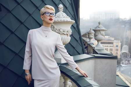 Beautiful sexy young business woman blond hair evening makeup wearing dress suit top  skirt high heels shoes business clothes for meetings walks summer fall collection perfect body shape glasses hotel Stock Photo