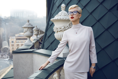Beautiful sexy young business woman blond hair evening makeup wearing dress suit top  skirt high heels shoes business clothes for meetings walks summer fall collection perfect body shape glasses hotel photo