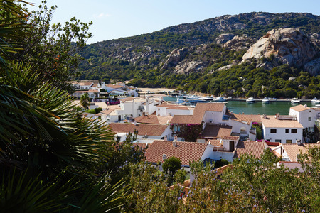roan: Beautiful summer view on the sea beach and mountain where is paved road and skyline with clouds and greenery trees from Italian Sardinia the best view on the island bay area from traveling vacation.