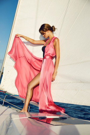 Beautiful young sexy brunette girl in a dress and makeup, summer trip on a yacht with white sails on the sea or ocean in the Gulf marine of the wind and the breeze in the sun tans romantic 版權商用圖片