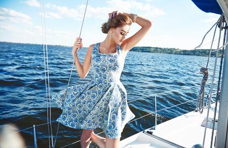 드레스와 메이크업에 아름 다운 젊은 섹시 갈색 머리 소녀, 로맨틱 태양 침침에서 바다 또는 바다 바람의 걸프 해양과 바람에 흰 돛 요트 여름 여행