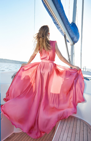 short wave: Beautiful young sexy brunette girl in a dress and makeup, summer trip on a yacht with white sails on the sea or ocean in the Gulf marine of the wind and the breeze in the sun tans romantic Stock Photo