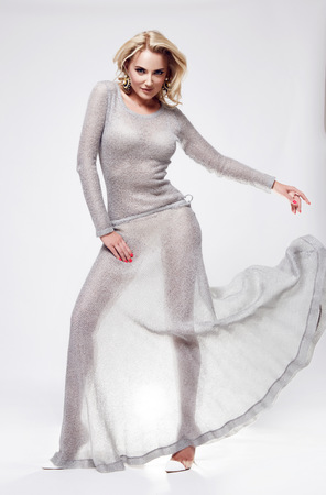 silver dress: Beautiful sexy young woman blond hair with evening make-up wearing fashion style long silver dress and high-heeled shoes clothes for meetings party and walks autumn collection perfect body shape