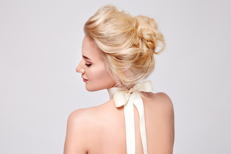 Tender fashion portrait of beautiful gentle young blond woman with silk bow on the neck cosmetics for body face hair pure natural beauty, organic and diet harmony, makeup 版權商用圖片