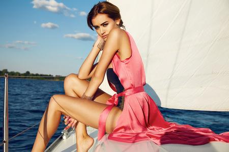Mooie jonge sexy brunette meisje in een jurk en make-up, zomer reis op een jacht met witte zeilen in de zee of oceaan in de Golf marine van de wind en de wind in de zon tans romantische