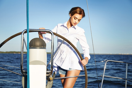 yacht people: Beautiful young sexy brunette girl in a dress and makeup, summer trip on a yacht with white sails on the sea or ocean in the Gulf marine of the wind and the breeze in the sun tans romantic Stock Photo
