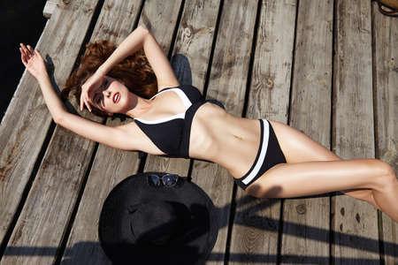 ombligo: Hermosa chica morena en buena forma con largo cabello oscuro y piel color canela labios rojos en la natación de moda sombrero suite de asientos se encuentran cerca de la piscina playa fluvial océano con agua verde sonrisa verano partido tan caliente