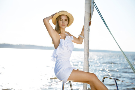 white girl: Beautiful young sexy brunette girl in a dress and makeup, summer trip on a yacht with white sails on the sea or ocean in the Gulf marine of the wind and the breeze in the sun tans romantic Stock Photo