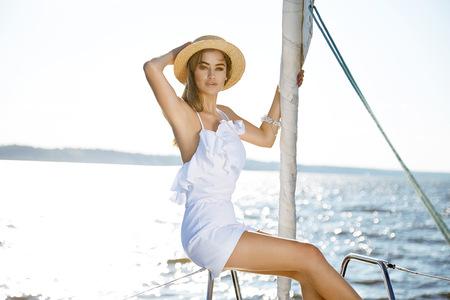 deportes nauticos: Hermosa joven morena sexy en un vestido y maquillaje, viaje de verano en un yate con las velas blancas en el mar o el océano en la marina del Golfo del viento y la brisa en los bronceados de sol románticas