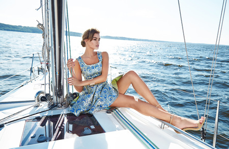 wind dress: Beautiful young sexy brunette girl in a dress and makeup, summer trip on a yacht with white sails on the sea or ocean in the Gulf marine of the wind and the breeze in the sun tans romantic Stock Photo