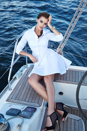 tans: Beautiful young sexy brunette girl in a dress and makeup, summer trip on a yacht with white sails on the sea or ocean in the Gulf marine of the wind and the breeze in the sun tans romantic Stock Photo