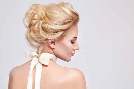 productos naturales: Retrato de la moda de licitación de la hermosa joven rubia dulce con el arco de seda en los cosméticos para la cara del cuello del cuerpo del pelo pura belleza natural, la armonía orgánica y la dieta, el maquillaje Foto de archivo