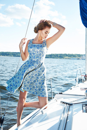 short: Beautiful young sexy brunette girl in a dress and makeup, summer trip on a yacht with white sails on the sea or ocean in the Gulf marine of the wind and the breeze in the sun tans romantic Stock Photo