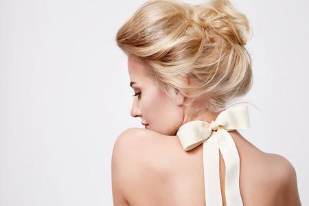 Anbud mode porträtt av vacker mild ung blond kvinna med siden rosett på halsen kosmetika för kroppen ansikte hår ren natur, organisk och kost harmoni, makeup