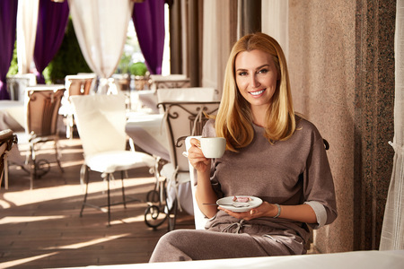the sun and shade: Beautiful young sexy girl blond woman with makeup and hairstyle sitting cafe restaurant bar drinking cappuccino latte tea interior summer terrace sun shade summer day relaxing breakfast meeting date Stock Photo