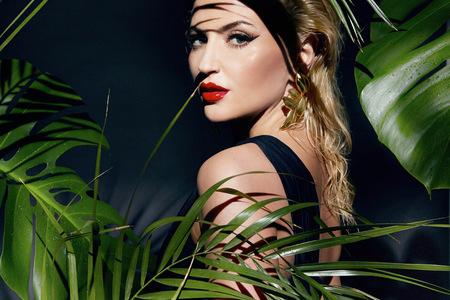 cuerpo humano: Modelo sexy joven hermosa mujer joven con la figura perfecta y el cuerpo de la piel bronceada aceite de maquillaje brillante y gotas de agua en la mano llevaba un mont�n de pulsera de hojas de palma en las sombras de la selva sol brillando Foto de archivo