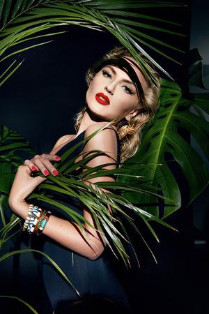 modelo: Modelo sexy joven hermosa mujer joven con la figura perfecta y el cuerpo de la piel bronceada aceite de maquillaje brillante y gotas de agua en la mano llevaba un montón de pulsera de hojas de palma en las sombras de la selva sol brillando Foto de archivo