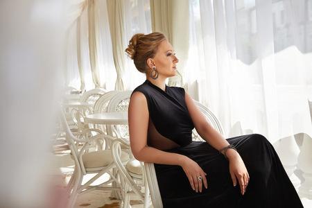 anochecer: Mujer sexy ojos azules rubia hermosa en un vestido rojo en pendientes con maquillaje diamantes noche, lápiz labial rojo, noche de lujo interior del partido del vestido restaurante del hotel