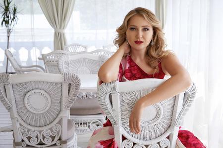 blonde yeux bleus: Belle femme sexy blonds yeux bleus dans une robe rouge en boucles d'oreilles diamants avec le maquillage du soir, rouge à lèvres rouge, soirée intérieur luxe robe parti d'hôtel restaurant Banque d'images