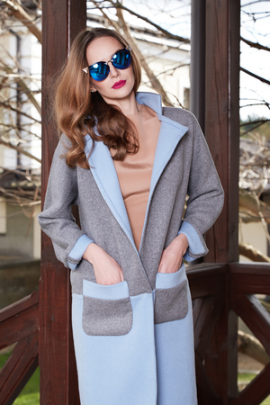 house coat: Beautiful fashionable young business woman wearing in autumn coat and sunglasses with hairdo and makeup walking on a street with fall near big house and trees without yellow leaves background