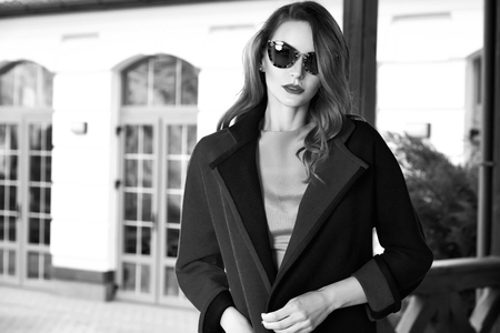 work clothes: Beautiful fashionable young business woman wearing in autumn coat and sunglasses with hairdo and makeup walking on a street with fall near big house and trees without yellow leaves background