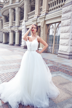 clothes organizer: Beautiful tender young woman sexy brunette bride in a luxury white wedding dress siting on the marble floor near the bushes on the Castle Summer happiness awaits the groom before the wedding ceremony