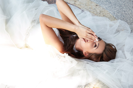Beautiful tender young woman sexy brunette bride in a luxury white wedding dress siting on the marble floor near the bushes on the Castle Summer happiness awaits the groom before the wedding ceremony