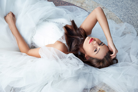 planner: Beautiful tender young woman sexy brunette bride in a luxury white wedding dress siting on the marble floor near the bushes on the Castle Summer happiness awaits the groom before the wedding ceremony