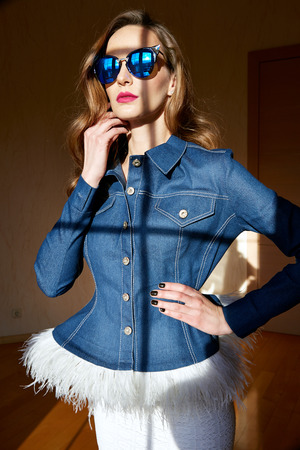 denim skirt: Beautiful young sexy woman with long blonde hair with natural make-up wearing casual autumn clothes denim jeans jacket with ostrich feathers and skirt from fall collection fashion style in sun shadow Stock Photo
