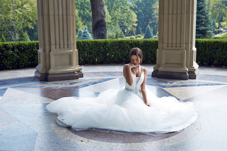 glans: Beautiful tender young woman sexy brunette bride in a luxury white wedding dress siting on the marble floor near the bushes on the Castle Summer happiness awaits the groom before the wedding ceremony