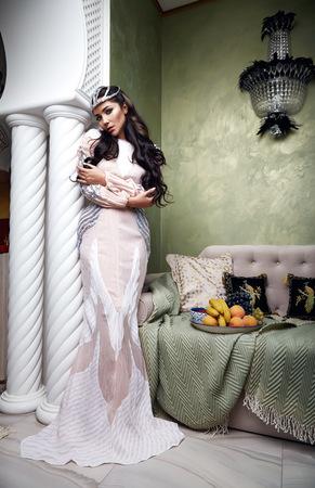長い黒髪ブルネットとシルクのレース、モロッコ スタイル ベルベット枕豪華な家具ファッション ハーレム妾果実の部屋寝室のイブニング ドレスの 写真素材