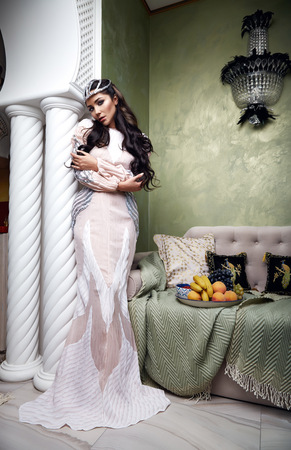 Beautiful young sexy woman with long dark hair brunette and decoration in evening dress of silk lace, room bedroom in Moroccan style velvet pillows luxurious furniture fashion harem concubine fruit Stock fotó