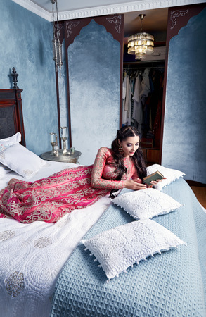 velvet dress: Beautiful young sexy woman with long dark hair brunette and decoration in evening dress of silk lace, room bedroom in Moroccan style velvet pillows luxurious furniture fashion harem concubine bed Stock Photo