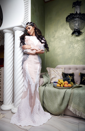 velvet dress: Beautiful young sexy woman with long dark hair brunette and decoration in evening dress of silk lace, room bedroom in Moroccan style velvet pillows luxurious furniture fashion harem concubine fruit Stock Photo