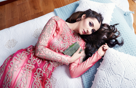 harem: Beautiful young sexy woman with long dark hair brunette and decoration in evening dress of silk lace, room bedroom in Moroccan style velvet pillows luxurious furniture fashion harem concubine bed Stock Photo