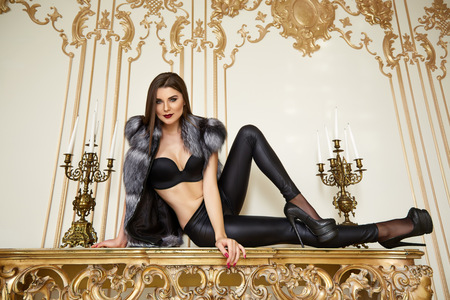 Beautiful sexy young brunette woman with long hair thin slender figure perfect body and pretty face make-up wearing leather djeans fur bra high heels gold interior luxury furniture party