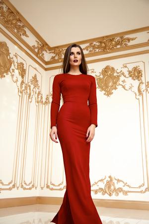 Bella sexy giovane donna bruna con i capelli lunghi sottili sottili figura del corpo perfetto e bel viso make-up indossando lunghe vestito di seta rossa piccola borsa tacchi oro interni mobili di lusso partito