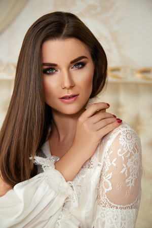 Beautiful sexy young brunette woman with long hair thin slender figure perfect body and pretty face make-up wearing white silk blouse gold interior luxury furniture party