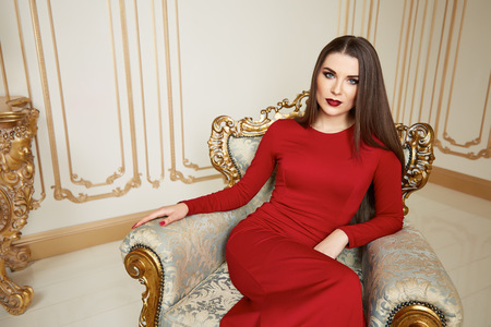 Beautiful sexy young brunette woman with long hair thin slender figure perfect body and pretty face make-up wearing long red silk dress small bag high heels gold interior luxury furniture party Imagens