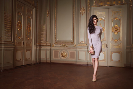 Beautiful sexy woman in elegant dress fashionable autumn Collection of spring long brunette hair makeup tanned slim body figure accessories interior luxury castle gold monogram baroque palace of Queen 版權商用圖片 - 48834918