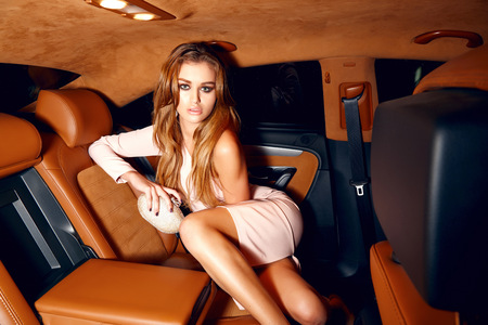 car accessory: Beautiful young sexy blonde wearing evening makeup in elegant fitting dress fashionable stylish sitting in cabin of expensive car comes out of it in hand  handbag luxury rich life going party concert