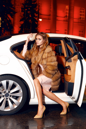 expensive car: Beautiful young sexy blonde wearing evening makeup in elegant fitting dress fashionable stylish sitting in cabin of expensive car comes out of it in hand  handbag luxury rich life going party concert