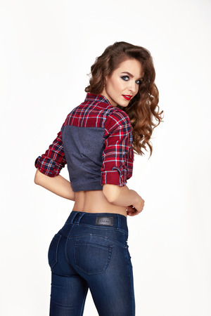 red jeans: Beautiful sexy young woman dressed in a black tight-fitting skinny denim jeans figure stands with his back to, brunette hair, make-up hair, red lipstick, clothing Stock Photo
