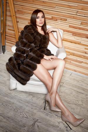 Mooie jonge sexy brunette vrouw draagt een korte jurk stijlvol design en modieuze bontjas, beige hakken schoenen lange dunne benen, lichaamsvorm zit op stoel, make-up, party mode-stijl winter Stockfoto