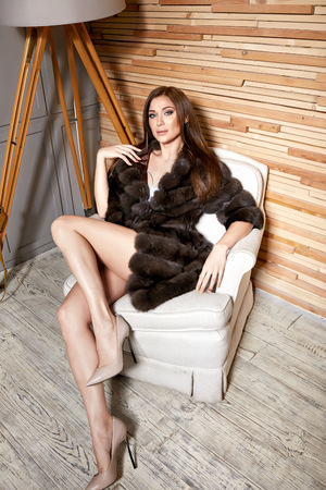 fur coat: Beautiful young sexy brunette woman wearing a short dress stylish design and fashionable fur coat, beige heels shoes long thin legs, body shape sits on chair, makeup, party fashion style winter