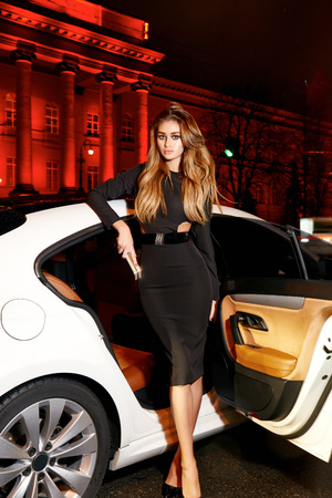 vip beautiful: Beautiful young sexy blonde wearing evening makeup in elegant fitting dress fashionable stylish sitting in cabin of expensive car comes out of it in hand  handbag luxury rich life going party concert