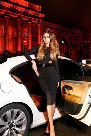 Schöne junge reizvolle Blondine trägt Abend Make-up im eleganten passendes Kleid modische stilvolle Sitz in der Kabine von teuren Auto kommt aus der es in der Hand Handtasche Luxus-reiches Leben Abendkonzert